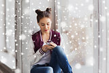 teenage girl with smartphone and earphones
