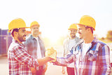 group of smiling builders shaking hands outdoors