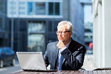 senior businessman with laptop at city street cafe