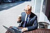 senior businessman with laptop drinking coffee