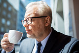 senior businessman drinking coffee on city street