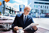senior businessman with newspaper drinking coffee