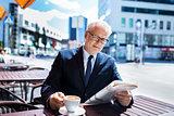 senior businessman with newspaper drinking coffee