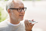 old man using voice command recorder on smartphone
