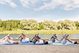 people making yoga in supine pigeon pose outdoors