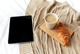tablet pc, coffee and croissant on bed at home