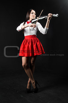 Slender woman playing the violin on a black background