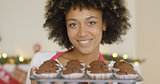 Smiling happy woman with tray of fresh muffins