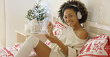 Cute young woman enjoying her music at Xmas