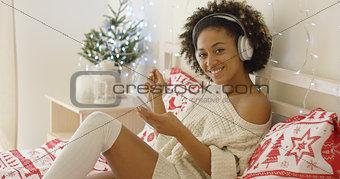 Cute young woman enjoying her music at Xmas