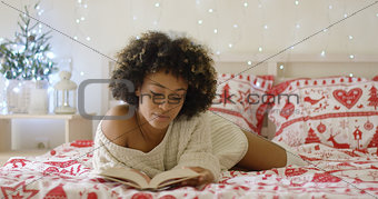Calm beautiful African woman reading in bed
