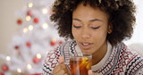 Young woman sipping a cup of hot lemon tea