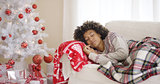 Woman sleeping on couch beside Christmas tree