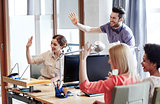 happy creative team waving hands in office