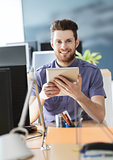 happy creative male office worker with tablet pc