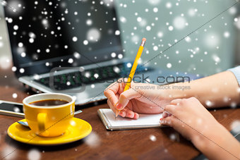 close up of woman writing to notebook with pencil