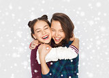 happy smiling teenage girls hugging over snow
