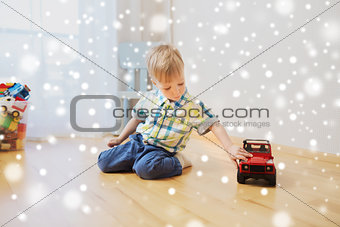 little baby boy playing with toy car at home