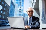 senior businessman with laptop at city street cafe