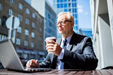 senior businessman with laptop drinking coffee