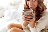 close up of happy woman with cocoa cup at home