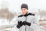 happy man with earphones and smartphone in winter