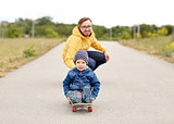 happy father and little son riding on skateboard
