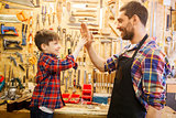 father and little son making high five at workshop