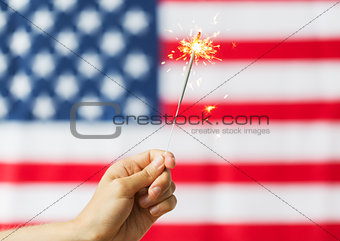 close up of hand with sparkler over american flag