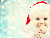 happy baby in santa hat over blue holidays lights