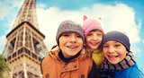 group of happy children hugging over eiffel tower