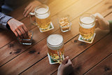 close up of hands with beer mugs at bar or pub
