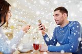 couple with smartphones drinking tea at cafe