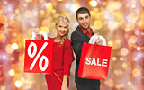 couple with sale sign on shopping bags