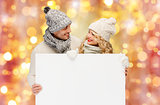 couple in winter clothes with blank white board