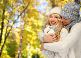 happy couple in warm clothes over autumn