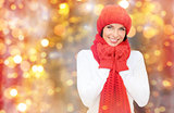 happy woman in hat, scarf and mittens over lights