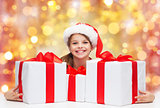 smiling girl in santa hat with christmas gifts