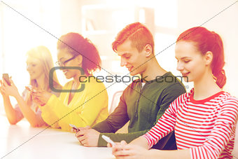 four smiling students with smartphones at school
