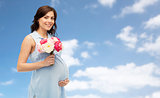 happy pregnant woman with flowers over blue sky