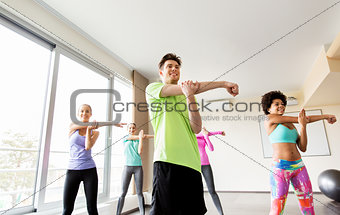 group of smiling people stretching in gym
