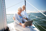 senior couple with tablet pc on sail boat or yacht