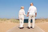 happy senior couple holding hands on summer beach
