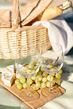picnic basket with wine glasses and food on beach