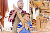 happy father and son with wood plank at workshop