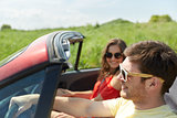 happy couple driving in cabriolet car at country