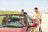 happy friends pushing broken cabriolet car
