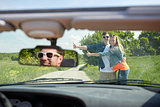couple hitchhiking and stopping car on countryside