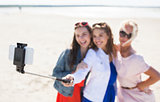 women with selfie stick and smartphone on beach