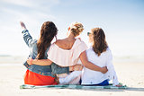 group of young women hugging on beach